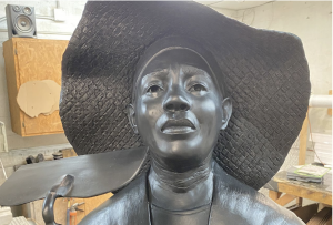 A bronze sculpture of a woman wearing a hat by artist Vinnie Bagwell
