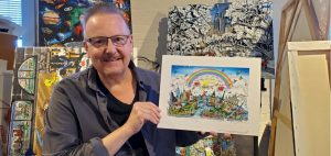 Man wearing glasses holds an artwork